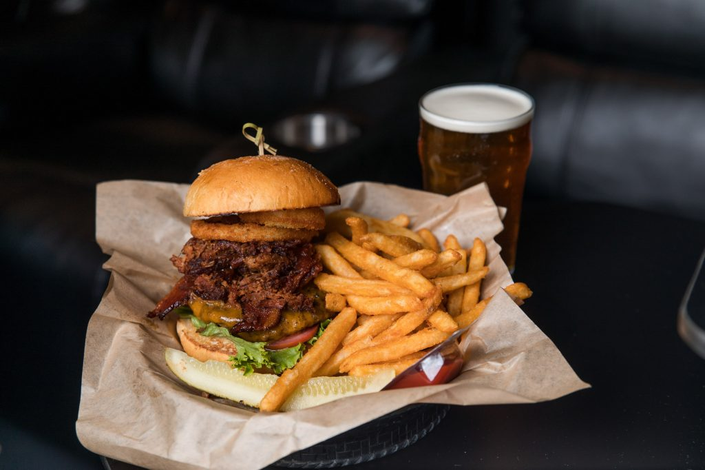 burger with brisket and onion rings at Flix Brewhouse with a beer, studio k10