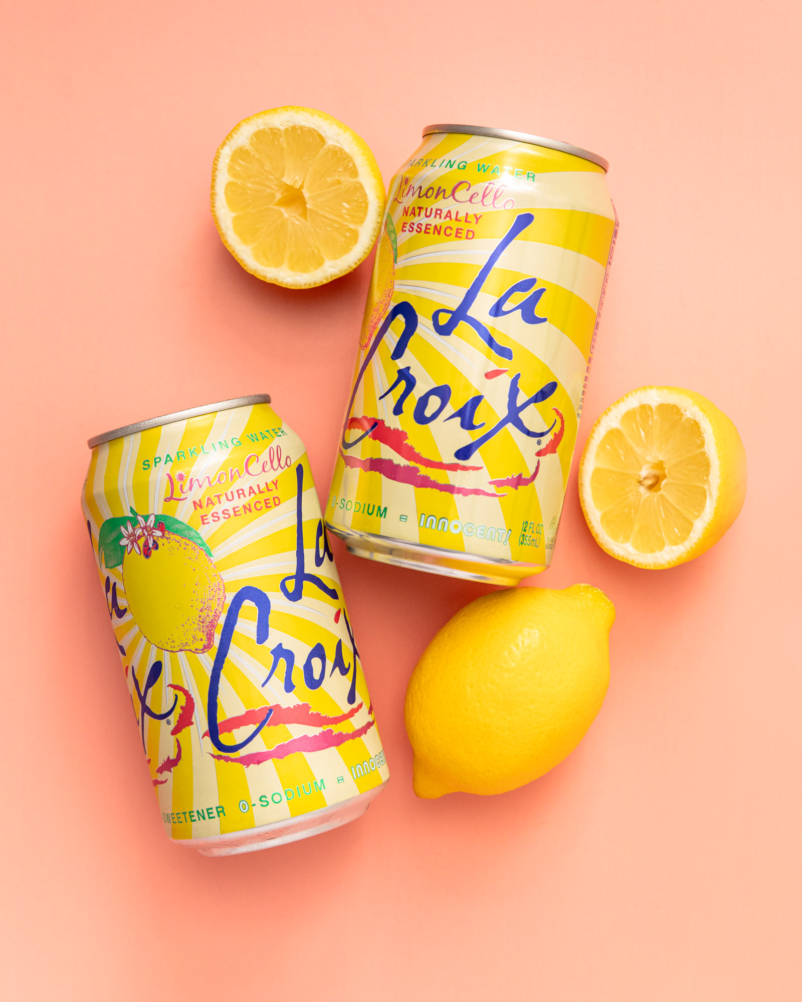 limoncello La Croix cans laying with lemons on a coral background, Studio K10